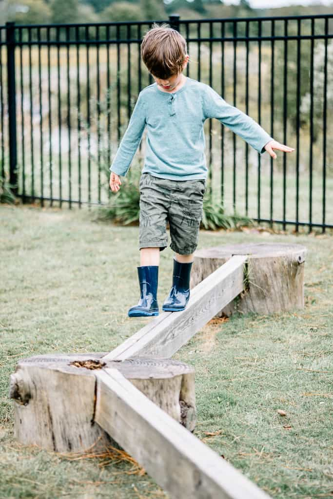 kindergarten student balances on the beam during recess