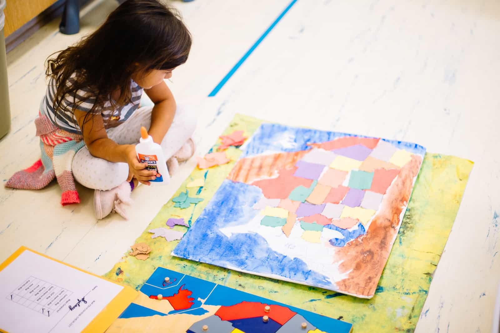 children's house montessori child working on a pin-push map of the united states