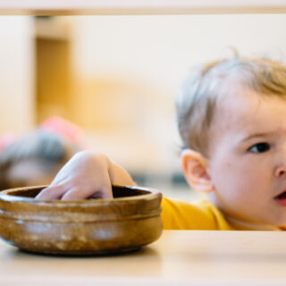 Montessori toddler taking a work from the shelf in the classroom